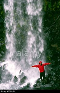 PICTURE CREDIT DOUG BLANE Carl Galvin in a red Mountain Equipment gore tex jacket under Svartifoss Waterfall in Iceland